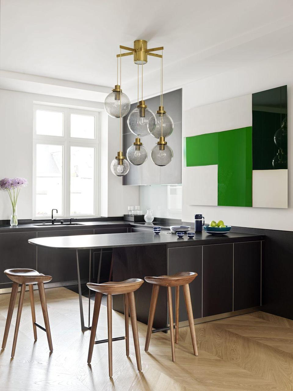 "<p>Would you ever guess this kitchen was originally built in the 1800s? While this <a href=""https://www.veranda.com/home-decorators/a30145144/le-berre-vevaud-paris-apartment/"" rel=""nofollow noopener"" target=""_blank"" data-ylk=""slk:dreamy Parisian apartment"" class=""link rapid-noclick-resp"">dreamy Parisian apartment</a> designed by <a href=""https://leberrevevaud.com/"" rel=""nofollow noopener"" target=""_blank"" data-ylk=""slk:Le Berre Vevaud"" class=""link rapid-noclick-resp"">Le Berre Vevaud</a> is rooted in historic, classical architecture, it's bright and modern design welcomes the home into the 21st century. Case in point is this sleek kitchen, with its focal point being 1950s blown-glass Lustre globes purchased at an auction from Piasa, which pairs well with contemporary art and the dramatic dark countertops and cabinetry. </p>"