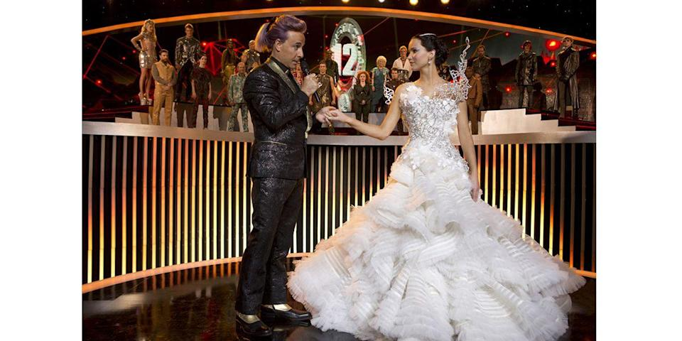 <p>Katniss Everdeen (Jennifer Lawrence) wore her fictional wedding dress to the Quarter Quell's opening ceremony upon President Snow's request. The gown was stunning and up to the Capitol's over-the-top standards—but its best feature showed itself only upon twirl.</p>