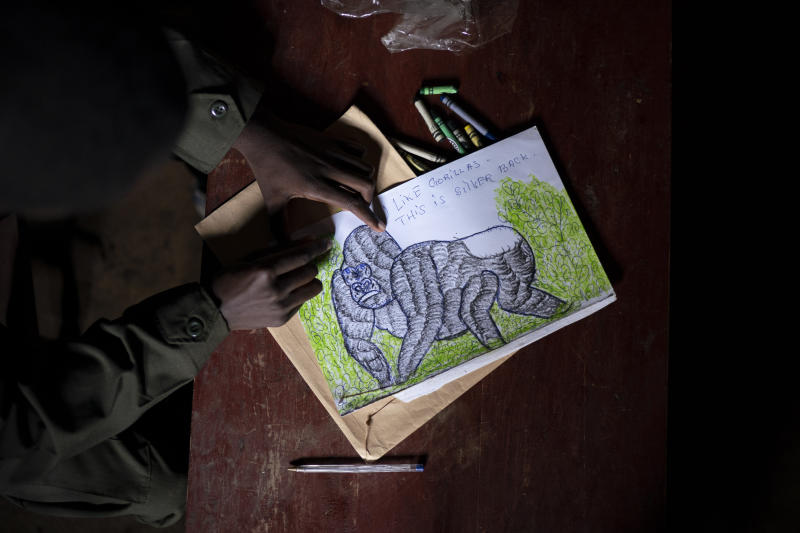 "Jean Claude Masengesho draws a silverback gorilla in Kinigi, Rwanda. He would like to someday become a tour guide, which would earn him about $320 monthly. The obstacle is that most tour guides have attended college, and the 21-year old isn't sure how his family can afford tuition. ""It's my dream, but it's very hard,"" he says. ""In this village, every young person's dream is to work in the park."" (Photo: Felipe Dana/AP)"