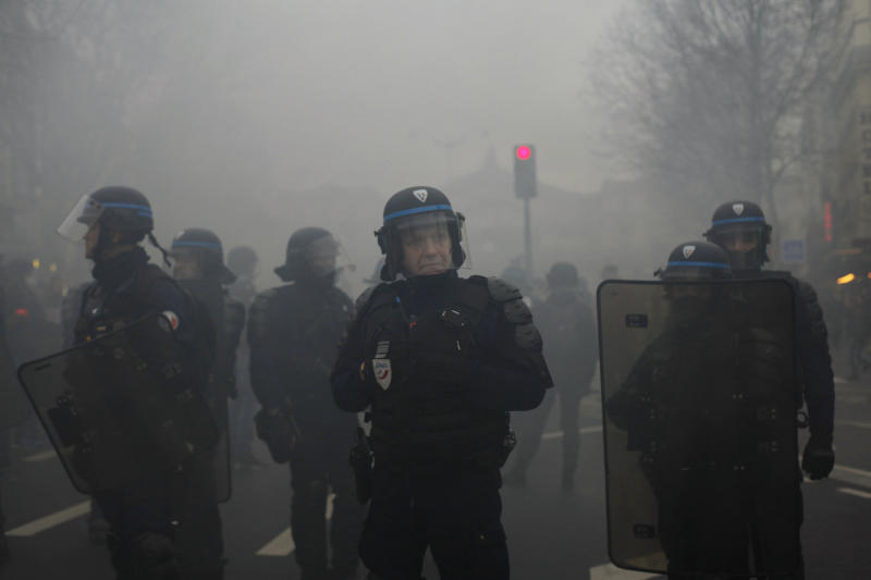 Riot police officers stand during a demonstration Thursday, Jan. 9, 2020 in Paris. Rail workers, teachers, doctors, lawyers and others joined a nationwide day of protests and strikes Thursday to denounce French President Emmanuel Macron's plans to overhaul the pension system. Banner reads: Striking until withdrawal. (AP Photo/Thibault Camus)