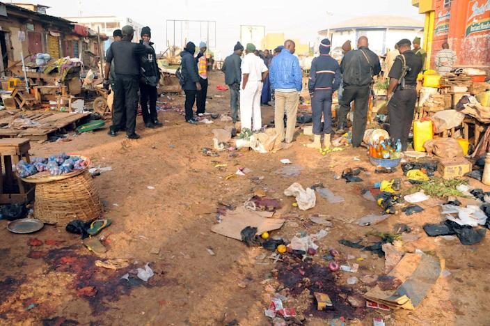 Nigerian security inspect the scene of a bomb blast at the Jos Terminus Market, on December 12, 2014 (AFP Photo/-)