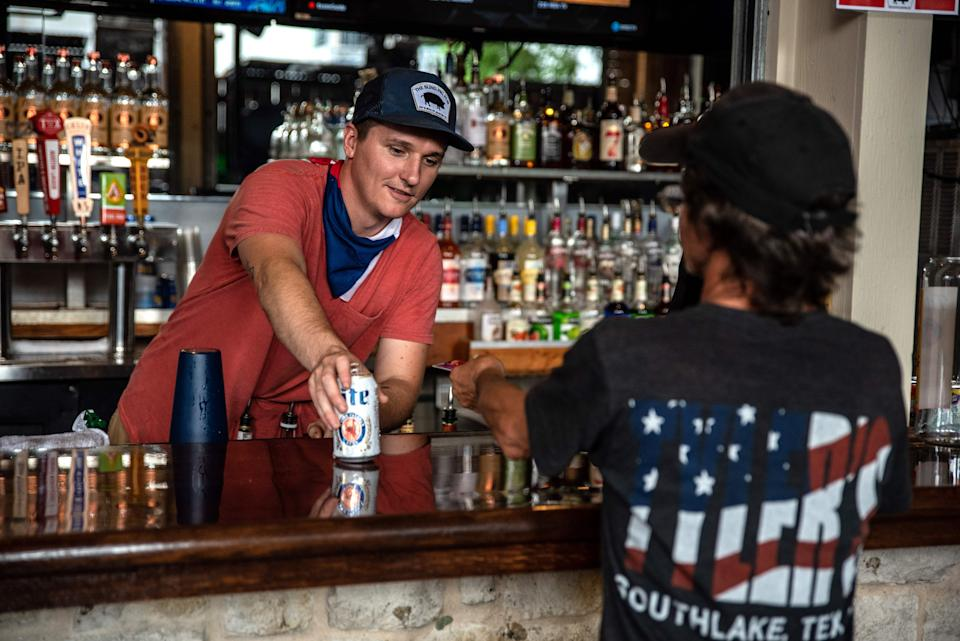 A bartender serves a drink to a customer at a bar in Austin, Texas on May 22, 2020. - Austin allowed bingo halls, bars and bowling alleys to reopen on Friday May 22. (Photo by Sergio Flores / AFP) (Photo by SERGIO FLORES/AFP via Getty Images)