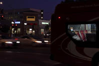 "A person wears a mask to prevent the spread of coronavirus on a city bus Tuesday, Nov. 24, 2020, in San Diego. California's health secretary urged people to say ""no"" to family and friends who want to gather for Thanksgiving, joining other officials in issuing dire warnings about the spread of the coronavirus. (AP Photo/Gregory Bull)"