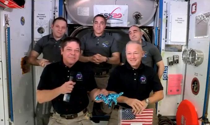 Crew Dragon astronauts Bob Behnken, front left, and Doug Hurley, front right, show off an American flag they plan to return to Earth that was left aboard the space station during the final shuttle mission in 2011. Also visible: Tremor, the toy dinosaur, that was given to Hurley and Behnken by their sons to serve as a reminder of home and as a zero-gravity indicator. Looking on were Expedition 63 crewmates Ivan Vagner, back left, commander Chris Cassidy, center, and Anatoly Ivanishin, back right. / Credit: NASA