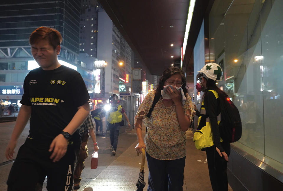 "Residents react to tear gas on the streets in Hong Kong on Sunday, Oct. 27, 2019. Hong Kong police fired tear gas Sunday to disperse a rally called over concerns about police conduct in monthslong pro-democracy demonstrations, with protesters cursing the officers and calling them ""gangster cops."" (AP Photo/Vincent Yu)"