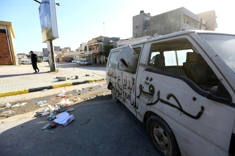 A damaged van lies on a road in the Hay al-Andalus neighbourhood of the Libyan capital Tripoli on March 14, 2017, following clashes between rival armed groups