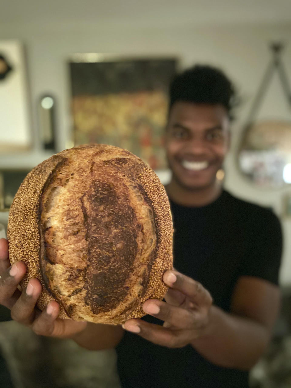 """Broadway performer Max Kumangai holds a loaf of sourdough bread at his apartment in New York. The triple threat from the musical """"Jagged Little Pill"""" has leaned into a fourth skill as the pandemic marches on: baking and selling his own sourdough. (Michael Lowney/Humpday Dough via AP)"""