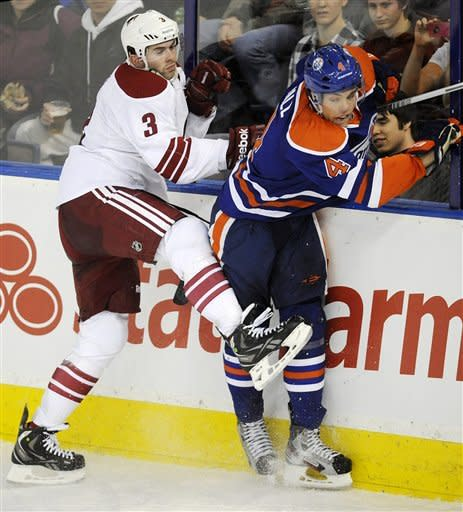 Phoenix Coyotes' Keith Yandle, left, checks the Edmonton Oilers' Taylor Hall during the second period of an NHL hockey game in Edmonton, Alberta, on Saturday, Feb. 25, 2012. (AP Photo/The Canadian Press, John Ulan)