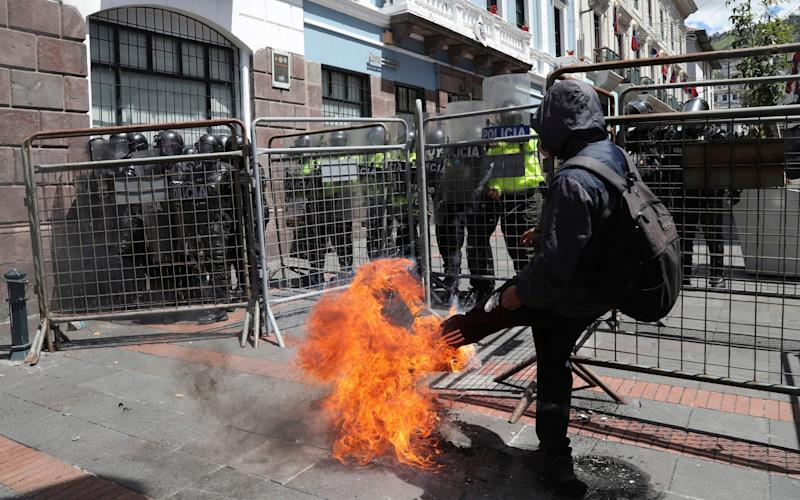 A protester kicks a burning tyre at a police barricade in Quito - AP