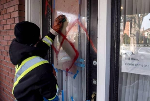 A graffiti removal worker cleans antisemitic graffiti, including a swastika, that was spray painted on the door of The Glebe Minyan in Ottawa, on Tuesday, Nov. 15, 2016. (Justin Tang/The Canadian Press - image credit)