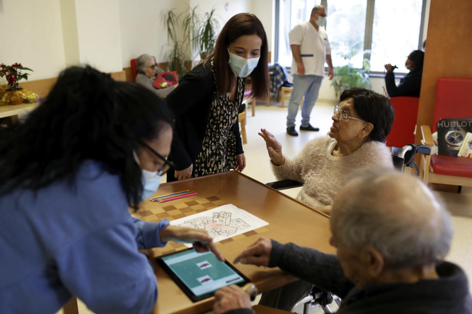 Technical director Diana Correia, center, listens to one of the residents at her care home in Amadora, outside Lisbon, Wednesday, Dec. 16, 2020. As a resurgence of the pandemic in the fall looked set to overwhelm Portuguese care homes like Correia's, and the country's public health service struggled to cope, the government mobilized all the resources it could. That included deploying military units. (AP Photo/Armando Franca)