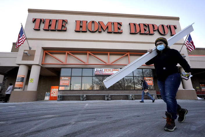 Passers-by walk near an entrance to a Home Depot home improvement store Sunday, Feb. 21, 2021, in Boston. The Home Depot's fiscal fourth-quarter sales surged 25% as the home improvement chain continues to meet the demands of consumers stuck at home and a resilient housing market. (AP Photo/Steven Senne)