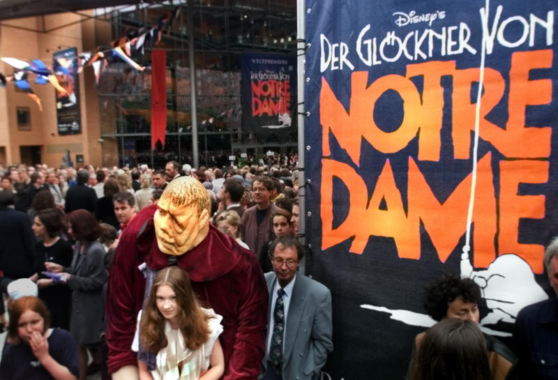 """FILE - In this Saturday June 5, 1999 file photo, a girl dressed as Esmeralda carries a dummy of the character Quasimodo as people go into the new concert hall at Potsdamer Platz in Berlin, Germany, before the world premiere of the musical """"The Hunchback of Notre Dame"""" later in the evening. The musical is a co-production of the U.S. American Disney company and the German musical company Stella. (AP Photo/Jan Bauer)"""