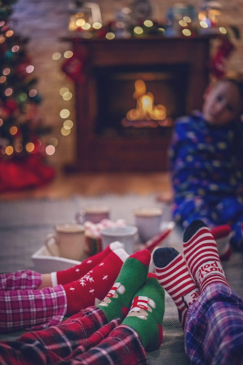 """<p>Throw on your matching Christmas jammies and your <a href=""""https://www.oprahmag.com/style/g28614181/fuzzy-christmas-socks/"""" rel=""""nofollow noopener"""" target=""""_blank"""" data-ylk=""""slk:fuzziest socks"""" class=""""link rapid-noclick-resp"""">fuzziest socks</a>, arrange sleeping bags under the tree, and have a family sleepover under the twinkling lights.</p>"""