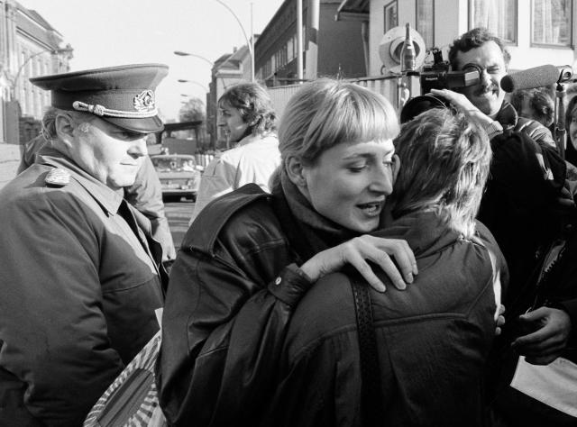 An East Berlin citizen embraces a West Berlin woman while an East German border soldier watches on at the Invalidenstrasse checkpoint after the opening of the East German border. (Photo: Fabrizio Bensch/Reuters)