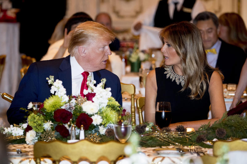 President Donald Trump and first lady Melania Trump talk at Mar-a-lago while there for Christmas Eve dinner in Palm Beach, Fla., Tuesday, Dec. 24, 2019. (AP Photo/Andrew Harnik)