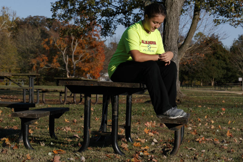 """Grace Brown, 14, adjusts her fitness tracker at the park where she does her jogging workouts for her """"online PE"""" class, in Alexandria, Va., Friday, Nov. 1, 2019. Brown chose to take """"online PE,"""" utilizing a fitness tracker, so that she could take a piano lab as an extra elective. (AP Photo/Jacquelyn Martin)"""