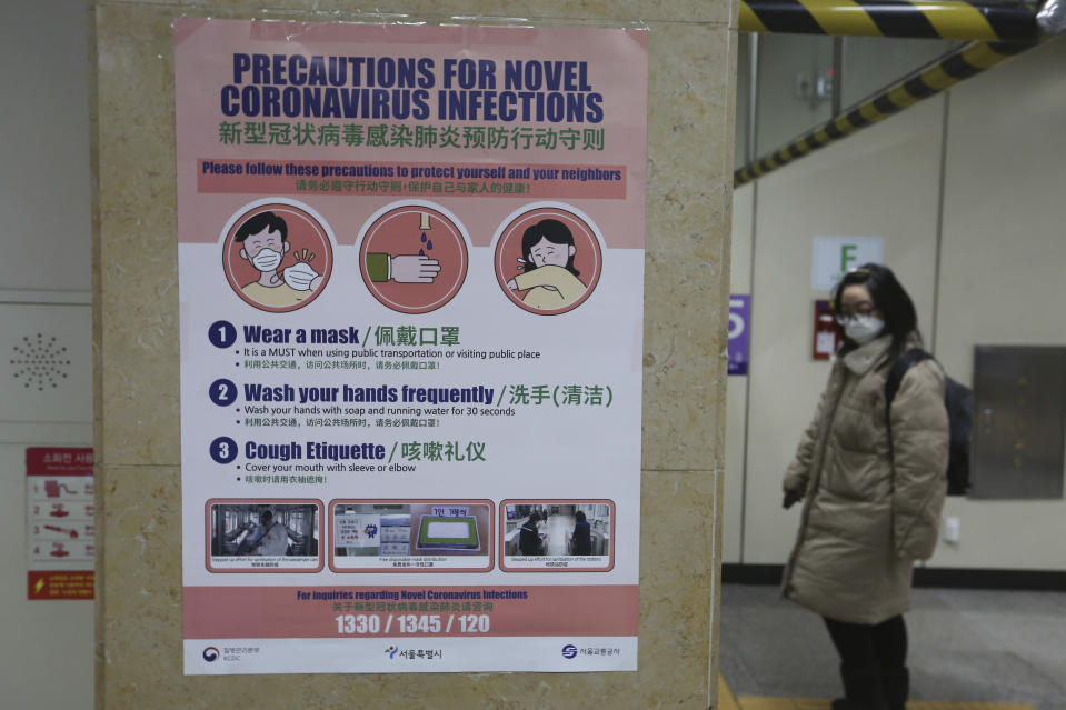 A woman passes by a poster about precautions against a new coronavirus at a subway station in Seoul, South Korea, Thursday, Feb. 6, 2020. Ten more people were sickened with a new virus aboard one of two quarantined cruise ships with some 5,400 passengers and crew aboard, health officials in Japan said Thursday, as China reported 73 more deaths and the World Health Organization appealed for more funds to help countries battle the spread of the disease. (AP Photo/Ahn Young-joon)