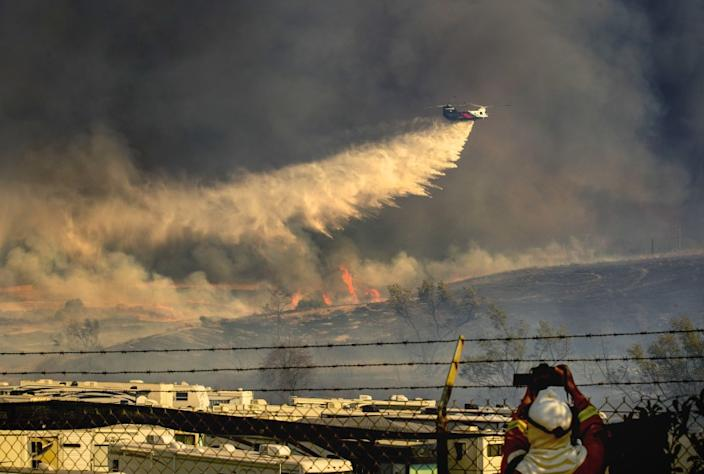 A helicopter makes a water drop on a Santa Ana wind-driven Bond fire
