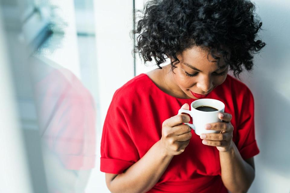 A close-up of a woman standing by the window holding a cup of coffee.