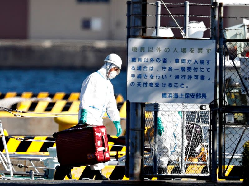 An officer in protective gears carry a luggage cases after people who were transferred from cruise ship Diamond Princess arrived at a maritime police's base in Yokohama