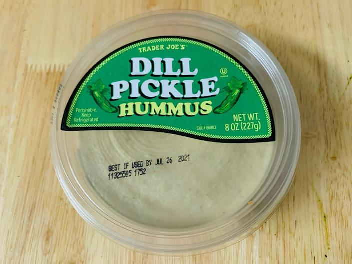 Trader joe's dill pickle hummus in it's original clear and green packaging on a light wood table