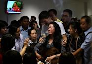 Family members of passengers onboard AirAsia flight QZ8501 react after watching news reports showing an unidentified body floating in the Java sea, inside the crisis-centre set up at Juanda International Airport