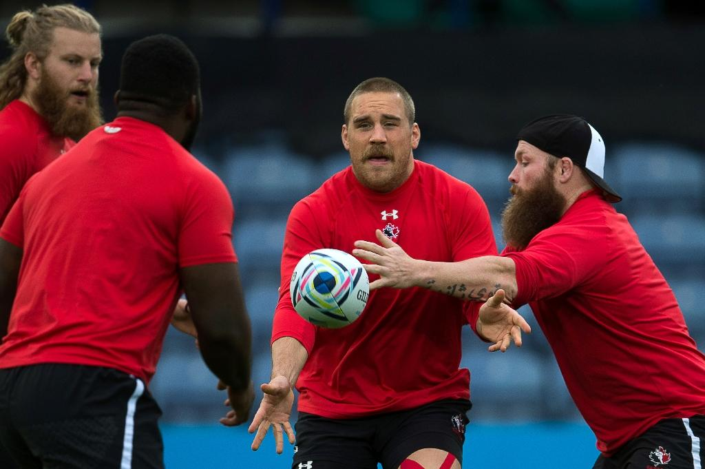 Canada's prop Jake Ilnicki (C) passes the ball next to Canada's hooker Ray Barkwill (R) during a captain's run training session in Leicester, central England, on October 5, 2015, on the eve of their 2015 Rugby Union World Cup match against Romania. AFP PHOTO / BERTRAND LANGLOIS RESTRICTED TO EDITORIAL USECanada's prop Jake Ilnicki (C) passes the ball next to Canada's hooker Ray Barkwill (R) during a captain's run training session in Leicester, central England, on October 5, 2015, on the eve of their 2015 Rugby Union World Cup match against Romania. AFP PHOTO / BERTRAND LANGLOIS RESTRICTED TO EDITORIAL USE (AFP Photo/BERTRAND LANGLOIS)