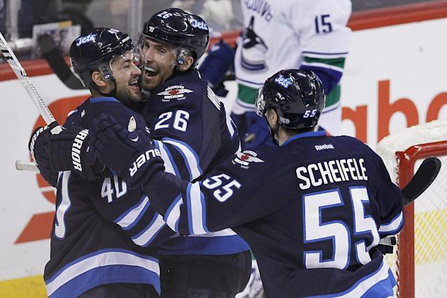 Winnipeg Jets' Devin Setoguchi (40) celebrates with Blake Wheeler (26) and Mark Scheifele (55) after scoring against the Vancouver Canucks during the third period of an NHL hockey game in Winnipeg, Manitoba, on Friday, Jan. 31, 2014. The Jets won 4-3. (AP Photo/The Canadian Press, John Woods)
