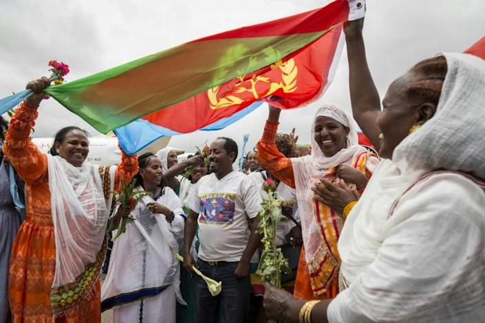 Joy: Eritrean women hold aloft the national flag in July 2018 to welcome passengers arriving from Ethiopia, a key step in the two rivals' path to peace (AFP Photo/MICHAEL TEWELDE)