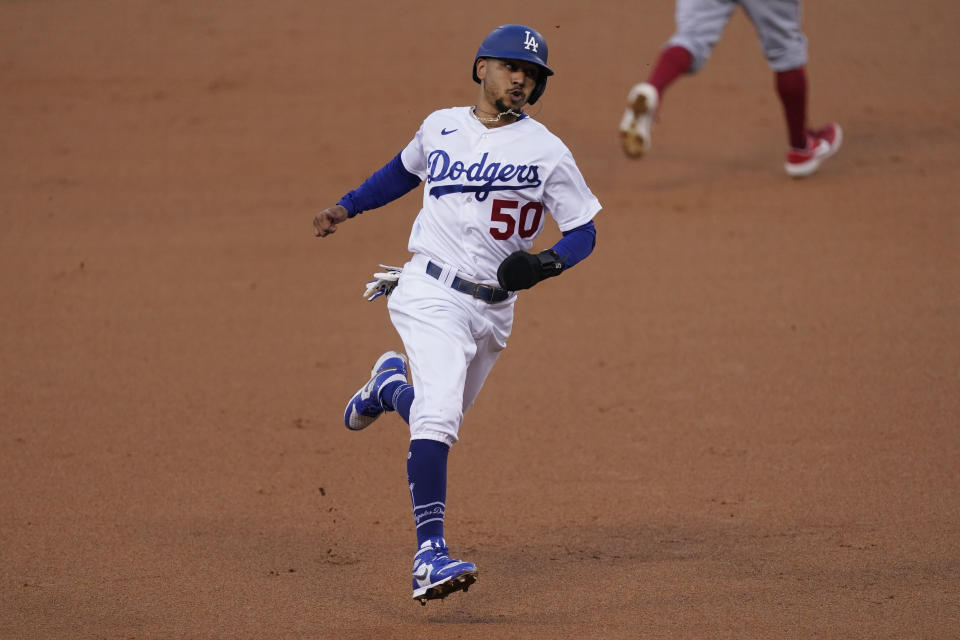 Los Angeles Dodgers' Mookie Betts runs to third base after Justin Turner singled to right field during the first inning of a baseball game against the Los Angeles Angels, Saturday, Sept. 26, 2020, in Los Angeles. (AP Photo/Ashley Landis)