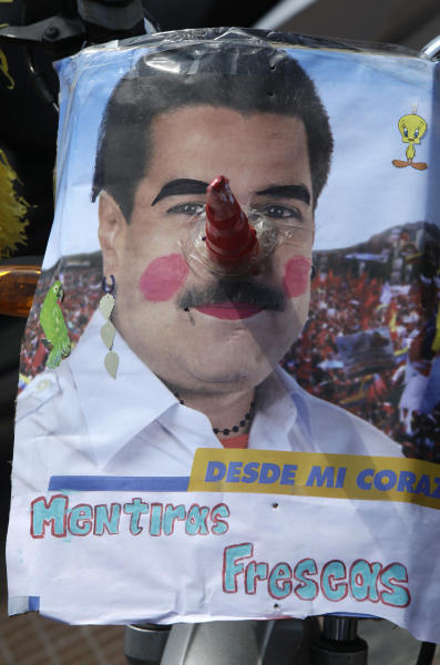 "A sign poking fun of ruling party presidential candidate Nicolas Maduro is seen during an opposition campaign rally ahead of next week end's presidential election in Caracas, Venezuela, Sunday, April 7, 2013. Tens of thousands of opposition candidate Henrique Capriles backers converged on a main avenue in downtown Caracas for Sunday's rally. The writting reads in Spanish ""from my heart, fresh lies.""(AP Photo/Enric Marti)"