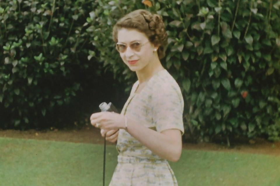 <p>A young Queen wearing sunglasses and holding a Cine camera on Christmas Day, 1953: In the middle of a gruelling 6 month tour</p> (The Queen Unseen/ITV/Factual Fiction)