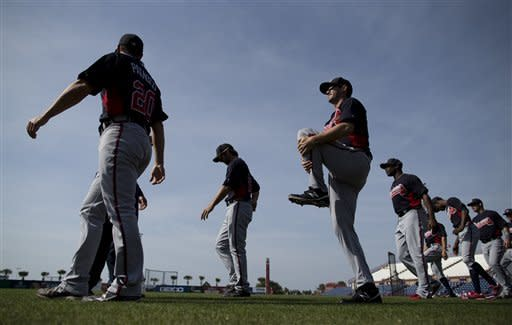 Atlanta Braves players stretch before the start of an exhibition spring training baseball game against the Washington Nationals on Monday, March 11, 2013, in Viera, Fla. (AP Photo/Evan Vucci)