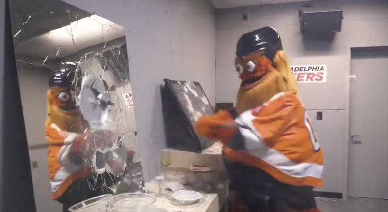 Gritty, the mascot of the Philadelphia Flyers, does a number on a mirror in the new rage room within the Wells Fargo Center. (Twitter//@NHLFlyers)