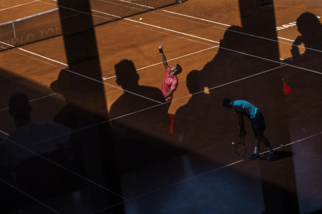 <p>Spain's Fernando Verdasco, in red, serves during a Madrid Open tennis match against Croatia's Marin Čilić, as Grigor Dimitrov from Bulgaria, in blue and reflected in the glass, prepares to serve to Fabio Fognini from Italy in the adjacent court, in Madrid, May 6, 2015. (AP Photo/Andres Kudacki) </p>