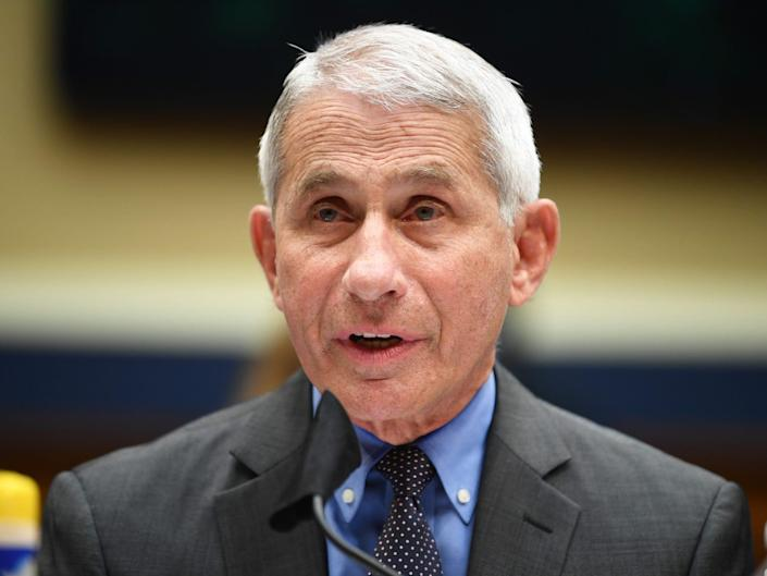 A file image of Dr. Anthony Fauci shows him wearing a blue shirt and black tie and grey suit jacket, speaking into a microphone.