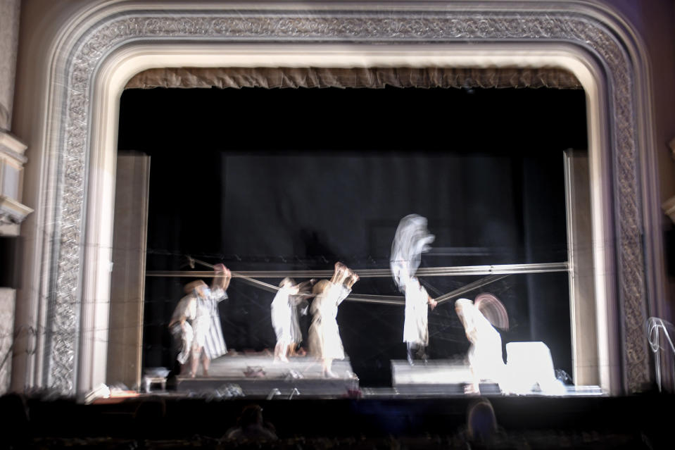 """In this photograph shot with a slow shutter speed actresses of the Jewish State Theatre, wearing face masks for protection against COVID-19 infection, perform during rehearsals for the premiere of the """"The Beautiful Days of My Youth"""" play, based on the diary of Romanian Jewish Holocaust survivor Ana Novac, in Bucharest, Thursday, Oct. 15, 2020. The latest première at the Jewish State Theater in the Romanian capital, Bucharest, explores the horrors of the Holocaust via a survivor's memories of the Auschwitz and Plaszow concentration camps. (AP Photo/Andreea Alexandru)"""