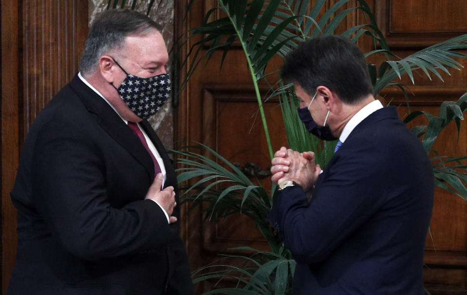 U.S. Secretary of State Mike Pompeo, left, and Italian Premier Giuseppe Conte wear a face mask to prevent the spread of COVID-19 as they greet each other on the occasion of their meeting at Chigi Palace, in Rome, Wednesday, Sept. 30, 2020. (Guglielmo Mangiapane/Pool Photo via AP)