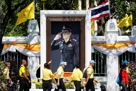 People walk in front of a portrait of Thailand's King Maha Vajiralongkorn during a rehearsal of his coronation procession which will take place next week in Bangkok, Thailand April 28, 2019. REUTERS/Jorge Silva