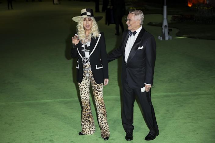 A woman in a black-and-white hat, jacket and cheetah-print pants and a man in a black suit posing on a green carpet
