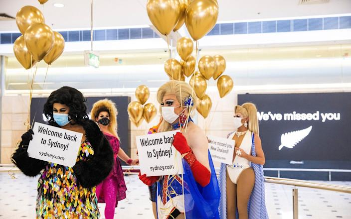 """Members of the """"welcome back drag committee"""" greet passengers arriving from New Zealand at Sydney International Airport, as the trans-Tasman travel bubble between New Zealand and Australia begins - Jenny Evans/Getty Images"""