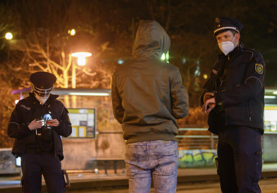 Police officers talk to a man during a curfew check at night in the Gorbitz district in Dresden, Germany, Saturday, Dec. 19, 2020. A hard lockdown has come into force in Germany to contain the coronavirus pandemic. (Robert Michael/dpa via AP)