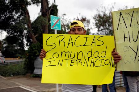 """FILE PHOTO: A man holds a banner that reads """"Thank you international community"""" near a warehouse where humanitarian aid for Venezuela is being stored near the Tienditas cross-border bridge between Colombia and Venezuela in Cucuta, Colombia, February 8, 2019. REUTERS/Marco Bello/File Photo"""