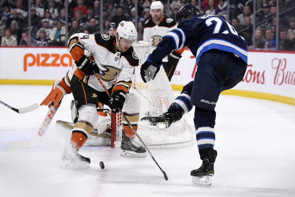 After losing his stick Winnipeg Jets' Blake Wheeler (26) kicks the puck past Anaheim Ducks' Cam Fowler (4) during the second period of an NHL hockey game, Sunday, Dec. 8, 2019 in Winnipeg, Manitoba. (Fred Greenslade/The Canadian Press via AP)