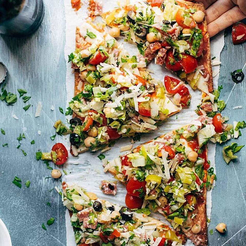 "<p>An Italian salad is a perfect solution for when you don't have time to grocery shop and instead just throw together whatever's left in the refrigerator. A simple cheese pizza gets a generous pile of chopped lettuce, vegetables, salami, olives, and Italian dressing.</p> <p><strong>Get the recipe:</strong> <a rel=""nofollow"" href=""https://pinchofyum.com/chopped-salad-pizza"">Chopped Salad Pizza</a></p>"