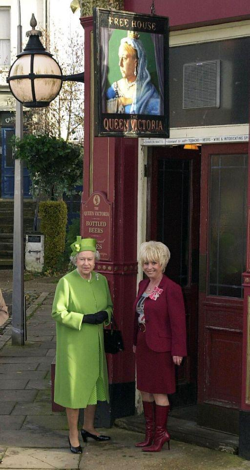<p>Her Majesty drops in on the Eastenders set at Elstree Studios. Here she stands outside the Queen Victoria pub with actress and longstanding cast member Barbara Windsor. (PA Archive) </p>