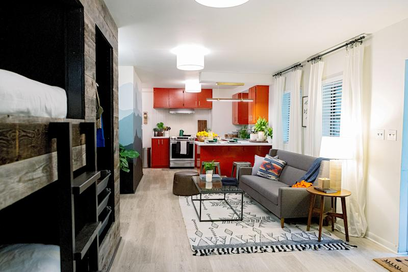 open living space with red kitchen and loft