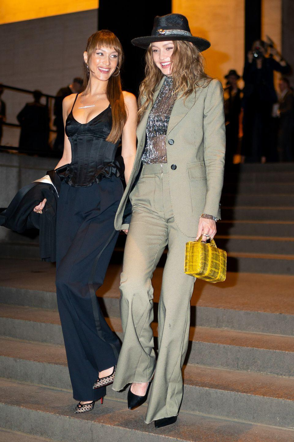 """<p>Both models <a href=""""https://www.harpersbazaar.com/celebrity/latest/a27066103/gigi-hadid-bella-hadid-marc-jacobs-wedding-guests/"""" rel=""""nofollow noopener"""" target=""""_blank"""" data-ylk=""""slk:wore suits"""" class=""""link rapid-noclick-resp"""">wore suits</a> to the nuptials. Gigi's hat is by <a href=""""https://www.yousseflahlou.com/"""" rel=""""nofollow noopener"""" target=""""_blank"""" data-ylk=""""slk:Youssef Lahlou"""" class=""""link rapid-noclick-resp"""">Youssef Lahlou</a>. Bella's earrings are <a href=""""https://vitafede.com/products/eclipse-hoop-earrings-1-7?variant=9449654648879"""" rel=""""nofollow noopener"""" target=""""_blank"""" data-ylk=""""slk:Vita Fede Eclipse hoops"""" class=""""link rapid-noclick-resp"""">Vita Fede Eclipse hoops</a>.</p>"""