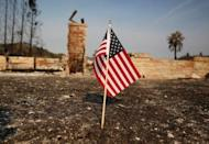 An American flag stands in front of a home destroyed after a wildfire tore through Santa Rosa, California, U.S., October 15, 2017. REUTERS/Jim Urquhart